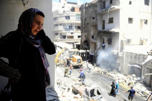 @REUTERS/Omar Sanadiki - A woman inspects a damaged site after a suicide and car bomb attack in south Damascus Shi'ite suburb of Sayeda Zeinab
